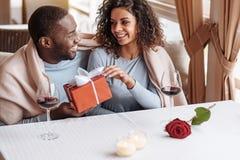 Ευχαριστημένο άτομο αφροαμερικάνων που δίνει το κιβώτιο στη φίλη του στοκ εικόνα με δικαίωμα ελεύθερης χρήσης