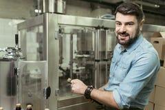 Ευχαριστημένο άτομο που ανοίγει ένα μπουκάλι του οινοπνεύματος στο ζυθοποιείο Στοκ Φωτογραφία
