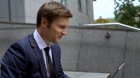 Ευχαριστημένο αρσενικό στο επιχειρησιακό κοστούμι που λειτουργεί στο lap-top στα σκαλοπάτια υπαίθρια, φιλοδοξίες στοκ φωτογραφία
