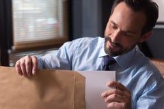 Ευχαριστημένο γενειοφόρο άτομο που εξετάζει τα έγγραφα στοκ εικόνα με δικαίωμα ελεύθερης χρήσης