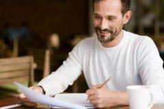 Ευχαριστημένο γενειοφόρο άτομο που κάνει τις σημειώσεις στον καφέ στοκ φωτογραφία με δικαίωμα ελεύθερης χρήσης