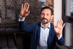 Ευχαριστημένο γενειοφόρο άτομο που πιέζει τους φοίνικές του στην εικονική οθόνη Στοκ Εικόνες