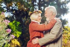 Ευχαριστημένο εύθυμο ηλικίας ζεύγος που αγκαλιάζει το ένα το άλλο στοκ εικόνες