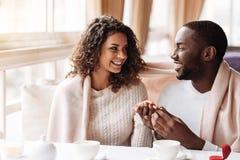 Ευχαριστημένο ζεύγος αφροαμερικάνων που παίρνει συμμετέχον στον καφέ στοκ εικόνα