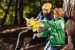 Ευχαριστημένο θετικό γενειοφόρο άτομο που βοηθά το γιο του στοκ φωτογραφία με δικαίωμα ελεύθερης χρήσης