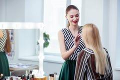 Ευχαριστημένο θετικό visagiste που εξετάζει τον πελάτη της στοκ φωτογραφία