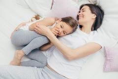 Ευχαριστημένο κορίτσι giggles χαρωπά όπως τα παιχνίδια με τη μητέρα της στο άνετο κρεβάτι, έχουν τα θετικά χαμόγελα στα πρόσωπα,  στοκ εικόνα