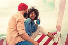 Ευχαριστημένο νέο κορίτσι που κλείνει τα μάτια της ακούοντας το φίλο της στοκ εικόνα με δικαίωμα ελεύθερης χρήσης