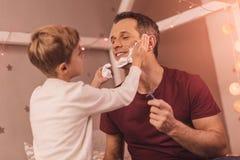 Ευχαριστημένο συμπαθητικό αγόρι που βοηθά τον πατέρα του για να ξυρίσει στοκ εικόνα