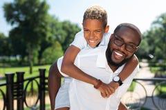 Ευχαριστημένο συμπαθητικό αγόρι που διατηρεί τον πατέρα του στοκ εικόνα με δικαίωμα ελεύθερης χρήσης