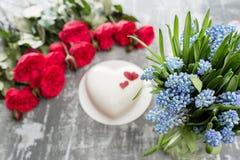 Ευχετήρια κάρτα ημέρας ή γενεθλίων βαλεντίνων Κέικ υπό μορφή κόκκινης καρδιάς Κόκκινα τριαντάφυλλα και επιδόρπιο στον εκλεκτής πο Στοκ εικόνα με δικαίωμα ελεύθερης χρήσης