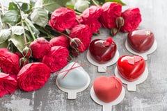 Ευχετήρια κάρτα ημέρας ή γενεθλίων βαλεντίνων Μέρος επιδόρπια υπό μορφή κόκκινης καρδιάς Κόκκινα τριαντάφυλλα και επιδόρπιο στον  Στοκ Φωτογραφίες