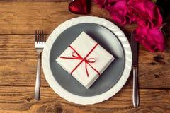 Ευχετήρια κάρτα ημέρας βαλεντίνων ` s του ST με το πιάτο, το μαχαίρι, το δίκρανο, το δώρο και τα τριαντάφυλλα Στοκ φωτογραφία με δικαίωμα ελεύθερης χρήσης