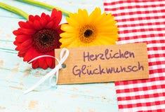 Ευχετήρια κάρτα με τα λουλούδια και το γερμανικό κείμενο, Herzlichen Glueckwunsch, συγχαρητήρια μέσων στοκ εικόνα