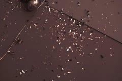 Ευχετήρια κάρτα Πάσχας χρώματος καφέ Χρυσό κομφετί στα χρωματισμένα φύλλα Χρυσό αυγό Πάσχας στην επιφάνεια Τοπ άποψη των ρυθμίσεω στοκ εικόνες