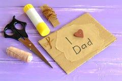 Ευχετήρια κάρτα χεριών με το μήνυμα Ι μπαμπάς αγάπης Ψαλίδι, κόλλα, σκοινί, νήμα, βελόνα Εμπνεύσεις τεχνών για τα παιδιά Στοκ Φωτογραφία