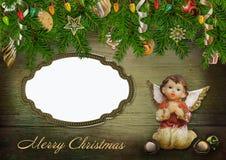 Ευχετήρια κάρτα Χριστουγέννων με τους κλάδους πεύκων, τις διακοσμήσεις αγγέλου, πλαισίων και Χριστουγέννων στο ξύλινο υπόβαθρο Στοκ φωτογραφίες με δικαίωμα ελεύθερης χρήσης