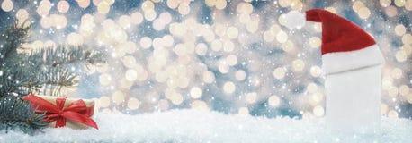 Ευχετήρια κάρτα Χριστουγέννων με το καπέλο, το έλατο και το δώρο Χριστουγέννων Στοκ εικόνα με δικαίωμα ελεύθερης χρήσης