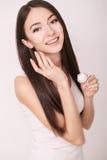 Εφαρμογή της καλλυντικής κρέμας Μια όμορφη νέα γυναίκα που εφαρμόζει το πρόσωπο moisturizer Προσοχή Scine του προσώπου και των χε Στοκ φωτογραφία με δικαίωμα ελεύθερης χρήσης
