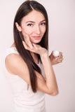 Εφαρμογή της καλλυντικής κρέμας Μια όμορφη νέα γυναίκα που εφαρμόζει το πρόσωπο moisturizer Προσοχή Scine του προσώπου και των χε Στοκ Εικόνα
