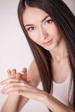 Εφαρμογή της καλλυντικής κρέμας Μια όμορφη νέα γυναίκα που εφαρμόζει το πρόσωπο moisturizer Προσοχή Scine του προσώπου και των χε Στοκ εικόνες με δικαίωμα ελεύθερης χρήσης