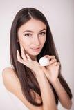 Εφαρμογή της καλλυντικής κρέμας Μια όμορφη νέα γυναίκα που εφαρμόζει το πρόσωπο moisturizer Προσοχή Scine του προσώπου και των χε Στοκ Εικόνες