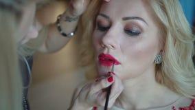 'Εφαρμογή' της καλλυντικής κόκκινης γυναίκας κραγιόν Όμορφο πρότυπο - κάνετε τα επάνω-χείλια η γυναίκα με το ραβδί φιλμ μικρού μήκους
