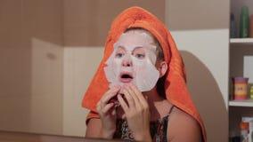 Εφαρμογή της καλλυντικής μάσκας στο πρόσωπο των νέων γυναικών Χρήση των μασκών προσώπου cosmetology φιλμ μικρού μήκους