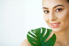 'Εφαρμογή' του διαφανούς βερνικιού δερμάτων προσοχής Όμορφο κορίτσι με τα πράσινα φύλλα επεξεργασία σαπουνιών πετρελαίου σύνθεσης στοκ εικόνα με δικαίωμα ελεύθερης χρήσης