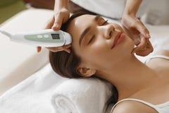 'Εφαρμογή' του διαφανούς βερνικιού δερμάτων προσοχής Γυναίκες που αναλύουν το του προσώπου δέρμα με τη συσκευή ανάλυσης _ Στοκ εικόνα με δικαίωμα ελεύθερης χρήσης
