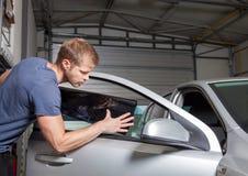 Εφαρμογή του φύλλου αλουμινίου βαψίματος επάνω σε ένα παράθυρο αυτοκινήτων Στοκ Εικόνες