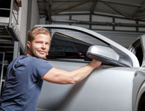 Εφαρμογή του φύλλου αλουμινίου βαψίματος επάνω σε ένα παράθυρο αυτοκινήτων Στοκ Φωτογραφία