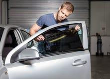 Εφαρμογή του φύλλου αλουμινίου βαψίματος επάνω σε ένα παράθυρο αυτοκινήτων Στοκ φωτογραφία με δικαίωμα ελεύθερης χρήσης