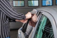 Εφαρμογή του φύλλου αλουμινίου βαψίματος σε ένα παράθυρο αυτοκινήτων Στοκ Εικόνα