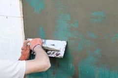 Εφαρμογή putty στον τοίχο που χρησιμοποιεί spatula Στοκ Εικόνες