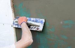 Εφαρμογή putty στον τοίχο που χρησιμοποιεί spatula Στοκ εικόνες με δικαίωμα ελεύθερης χρήσης