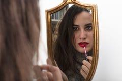 εφαρμόζοντας το όμορφο κραγιόν προσώπου κινηματογραφήσεων σε πρώτο πλάνο που φαίνεται κόκκινη s γυναίκα καθρεφτών Στοκ φωτογραφίες με δικαίωμα ελεύθερης χρήσης