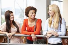Εφηβικά κορίτσια σπουδαστών που κουβεντιάζουν στο εσωτερικό Στοκ Φωτογραφίες
