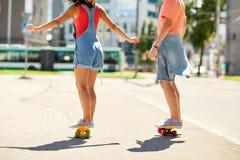 Εφηβικά οδηγώντας skateboards ζευγών στην οδό πόλεων Στοκ Εικόνες