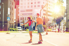 Εφηβικά οδηγώντας skateboards ζευγών στην οδό πόλεων Στοκ Φωτογραφίες