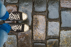 Εφηβικά πόδια στα πάνινα παπούτσια στο υγρό πεζοδρόμιο Στοκ Εικόνες