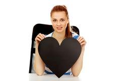 Εφηβική γυναίκα που κρατά τη μαύρη καρδιά εγγράφου Στοκ εικόνα με δικαίωμα ελεύθερης χρήσης