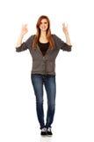 Εφηβική γυναίκα που παρουσιάζει δύο ΕΝΤΑΞΕΙ σημάδια Στοκ Φωτογραφία