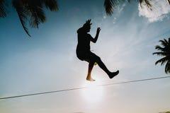 Εφηβική εξισορρόπηση στο slackline με την άποψη ουρανού Στοκ Εικόνες