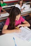 Εφηβική μαθήτρια που γράφει στο γραφείο στοκ εικόνες με δικαίωμα ελεύθερης χρήσης