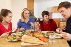 Εφηβική οικογένεια που έχει το όρισμα ταυτόχρονα τρώγοντας το μεσημεριανό γεύμα Στοκ φωτογραφία με δικαίωμα ελεύθερης χρήσης