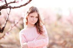 Εφηβική στάση χαμόγελου στον κήπο ροδάκινων Στοκ Εικόνα