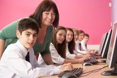 Εφηβικοί σπουδαστές στην κλάση ΤΠ που χρησιμοποιεί τους υπολογιστές Στοκ Εικόνες