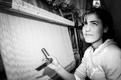 Εφηβικός εργαζόμενος με τον υφαίνοντας αργαλειό Στοκ Εικόνες