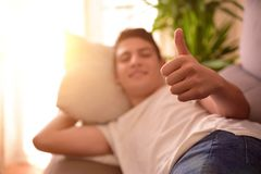 Εφηβικός σε έναν καναπέ που κάνει στο σπίτι το εντάξει σημάδι Στοκ Εικόνες